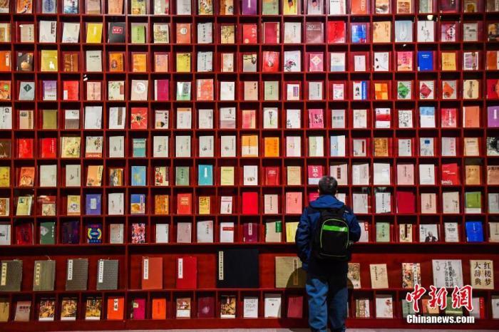 """资料图:此前,""""隻立千古——《红楼梦》文化展""""在中国国家博物馆举行。观众正在参观各个版本的《红楼梦》。<a target='_blank' href='http://fyand.com/'>中新社</a>发 麦田 摄"""