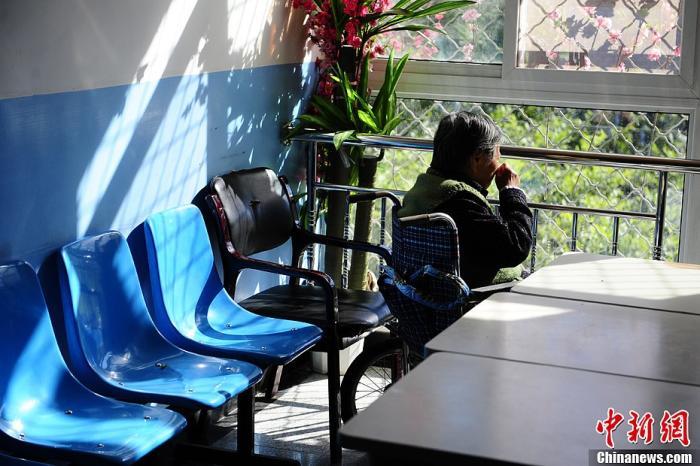 资料图:在北京市郊区一家专业收治阿尔茨海默病的专科医院,一位患有该病症的老人正在轮椅上晒太阳。中新社发 崔楠 摄