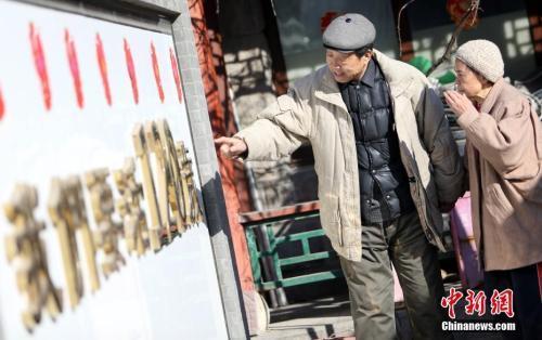 资料图:一位老人陪患有老年痴呆的老伴散步,考她墙上的字。中新社记者 杨可佳 摄