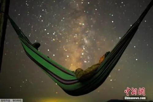 当地时间2018年8月13日,马其顿,科济亚克山一名女孩躺在吊床上,观看英仙座流星雨。