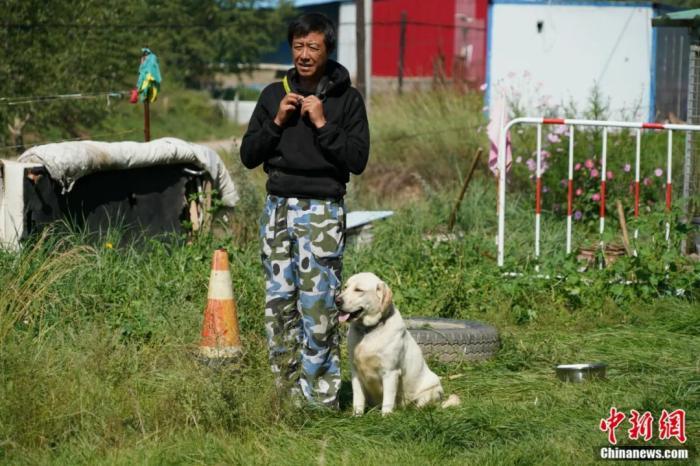 图为训导员朱勇和搜救犬。文思睿 摄