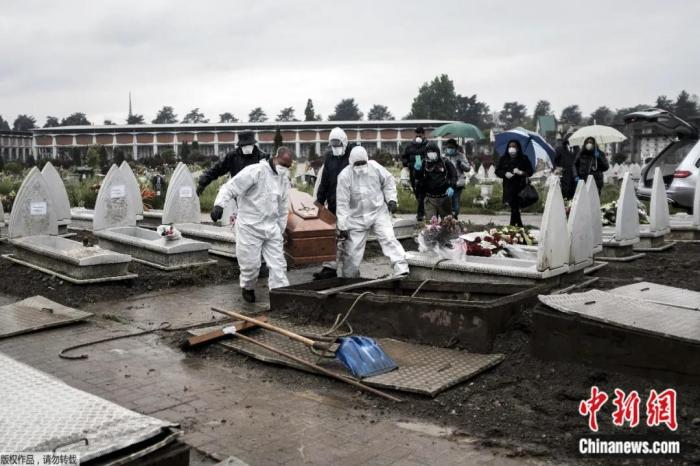 4月20日,在意大利都灵的墓地,身穿防护服的殡仪馆工作人员搬运棺材准备下葬。