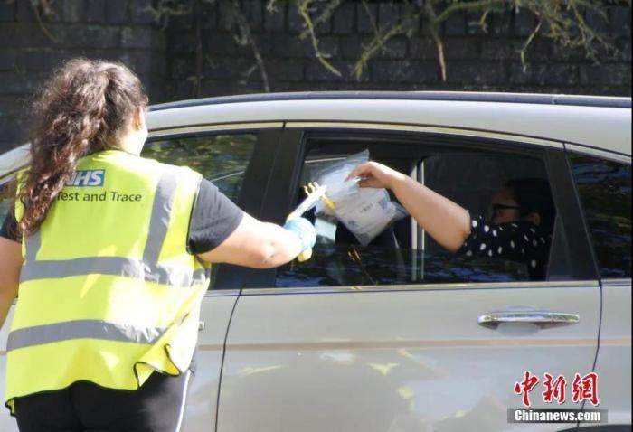 英国伦敦一核酸检测人员隔着车窗收取受检者的受检生物样本。中新社发 高天胤 摄