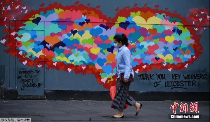 当地时间6月29日,英国莱斯特市中心,行人走过一幅为感谢疫情中做出贡献的工作人员而作的壁画。