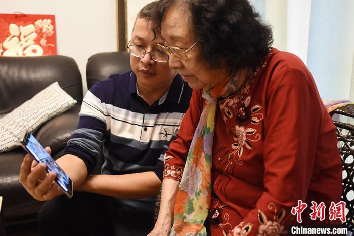 潮剧名伶姚璇秋在手机上观看总书记在潮州考察时的短视频。初绛