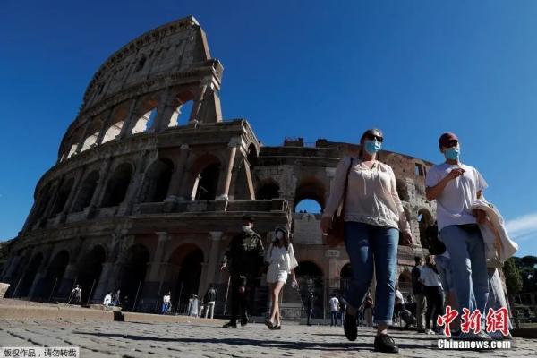 资料图:当地时间10月8日,意大利首都罗马,民众佩戴口罩走过斗兽场。