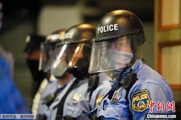 当地时间2020年10月27日,美国宾夕法尼亚州费城警方在民众进行示威抗议现场执勤。