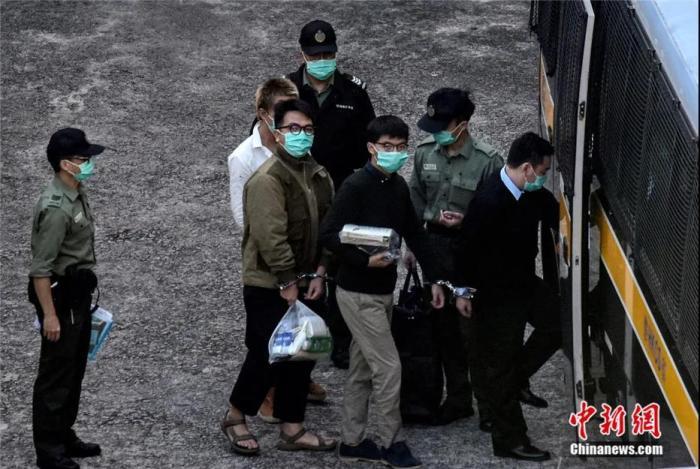 12月2日上午8时许,黄之锋(右三)及林朗彦(左二)在香港荔枝角收押所被押上惩教署车辆移送法院。记者 李志华 摄