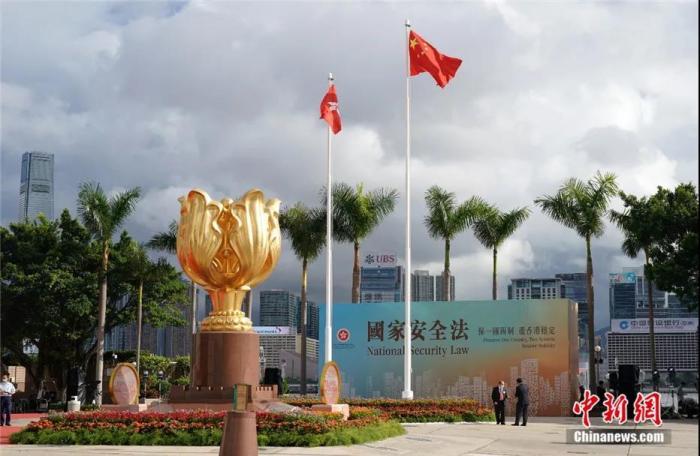 """资料图:香港国安法实施让香港结束了""""港独""""猖狂、""""黑暴""""肆虐的动荡局面,迎来了由乱转治的重大转折。图为2020年7月1日,香港国安法实施后的第一个早晨,金紫荆广场的金紫荆雕塑在阳光下熠熠生辉。记者 张炜 摄"""