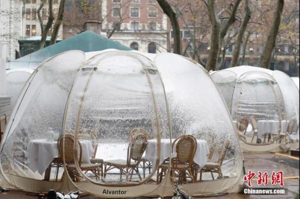 """资料图:当地时间12月9日,美国纽约迎来今冬�e首场降雪,布莱恩�锕�园的户外用餐""""泡泡屋""""覆盖白雪。中新⌒社记者 廖攀 摄"""