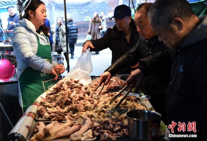 """资料图:""""冬至""""节气当天,重庆一老字号羊肉馆生意火爆,众多市民排长队等待进补,也有市民将羊肉买回家自己炖煮。 周毅 摄"""