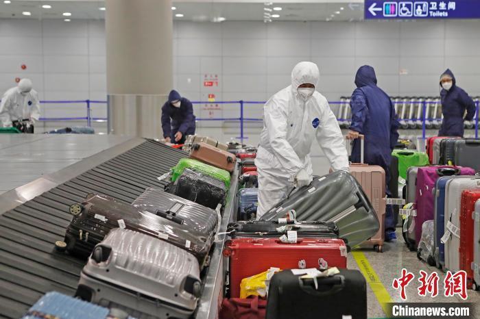 资料图:上海浦东机场工作人员正在T2航站楼入境到达行李转盘,将行李按照出发地进行摆放。 殷立勤 摄