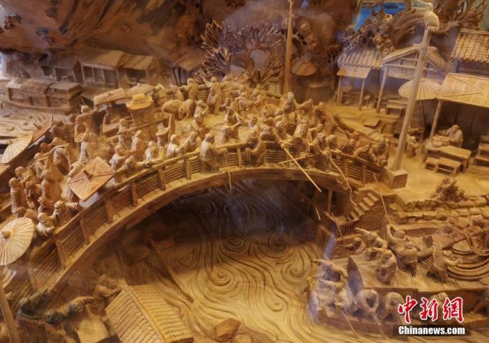 资料图:此前,重庆男子花两年半时间在崖柏上雕刻的立体版《清明上河图》完工。钟欣 摄