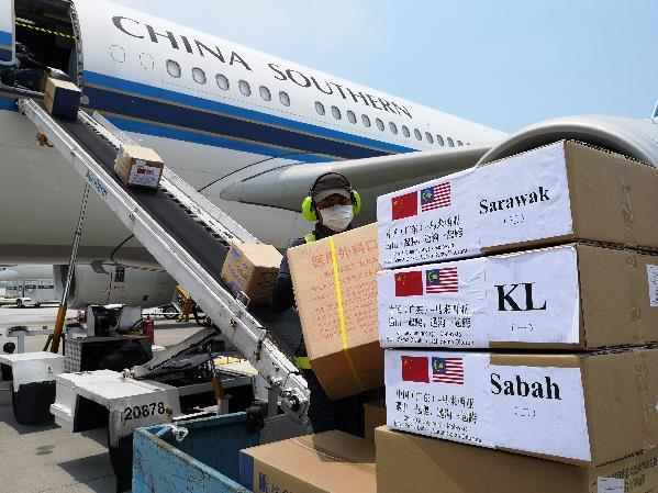 4月18日,在马来西亚吉隆坡国际机场,地勤人员搬运中国政府向马来西亚派遣的抗疫医疗专家组带来的物资。新华社发(中国驻马来西亚大使馆供图)