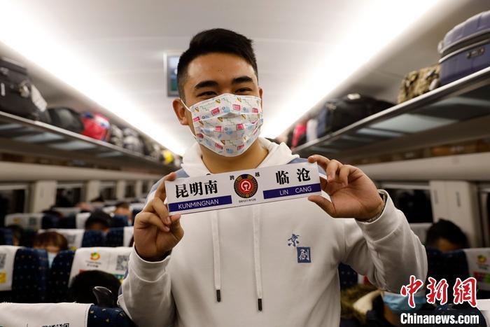 """图为在由昆明开往临沧的D8126列车上,乘客展示自制""""站牌""""。 中新社记者 李嘉娴 摄"""