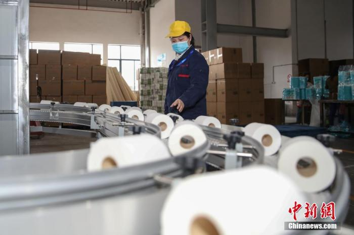 資料圖:4月24日,某紙業有限公司的工人在檢查衛生紙生產流水線的質量。 <a target=