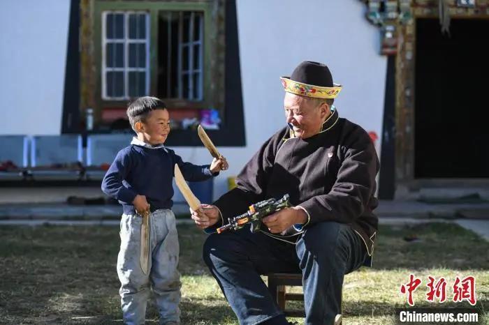 资料图:米林县扎西绕登乡彩门村64岁的洛桑带着孙子巴桑在院子的草地上玩耍。何蓬磊 摄