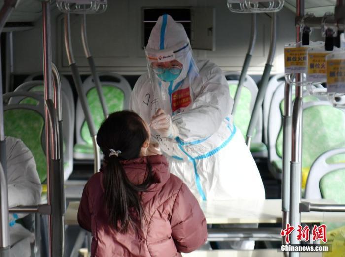 """资料图:医护人员在""""核酸采样流动车""""上为市民采集咽拭子。翟羽佳 摄"""