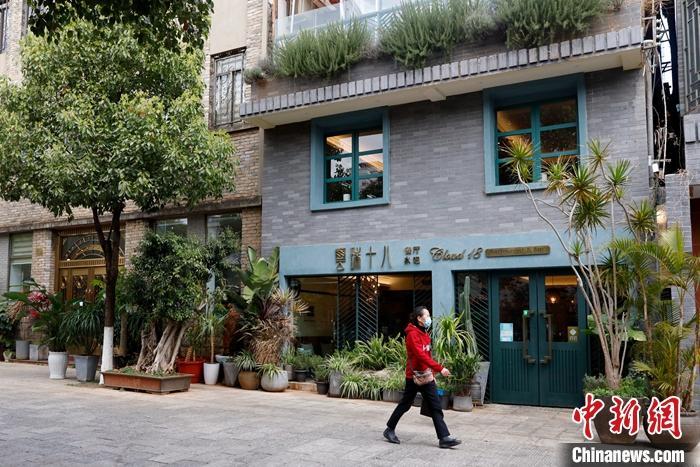 2月25日,市民从阿卿开的泰餐店门前走过。中新社记者 李嘉娴 摄
