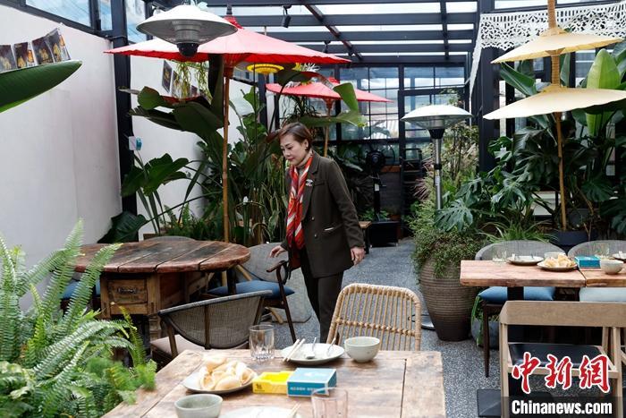 2月25日,阿卿在餐厅整理桌椅。2006年,泰国人阿卿在昆明世博园附近开了泰餐厅。中新社记者 李嘉娴 摄