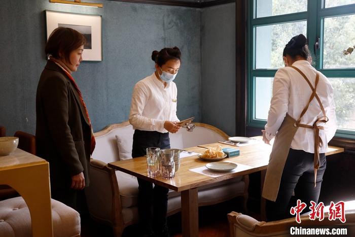 2月25日,阿卿在餐厅内指导服务员收拾餐桌摆放餐具。中新社记者 李嘉娴 摄