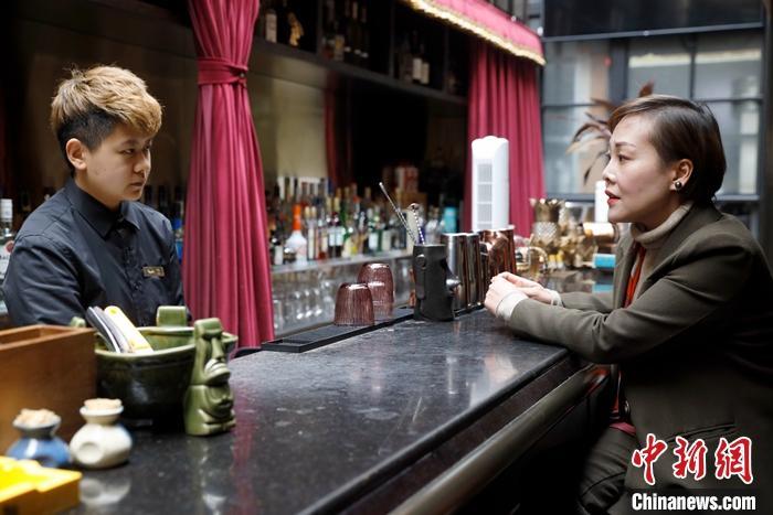 2月25日,阿卿(右)询问服务员近期饮品销售情况。2006年,泰国人阿卿在昆明世博园附近开了泰餐厅。中新社记者 李嘉娴 摄