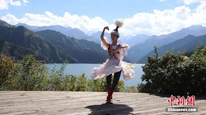 资料图:身着哈萨克族服饰的姑娘在新疆天山天池边跳舞。王小军 摄