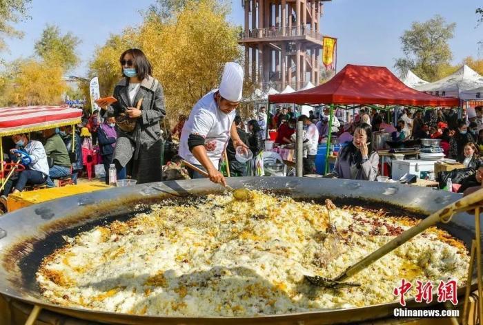 资料图:新疆沙雅胡杨节,一口直径达3米的大锅在现场制作当地美食抓饭。中新社记者 刘新 摄