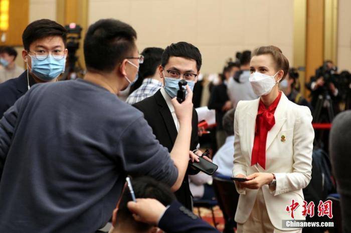 图为3月7日记者会开始前,中外记者在梅地亚中心多功能厅内交流。 中新社记者 蒋启明 摄