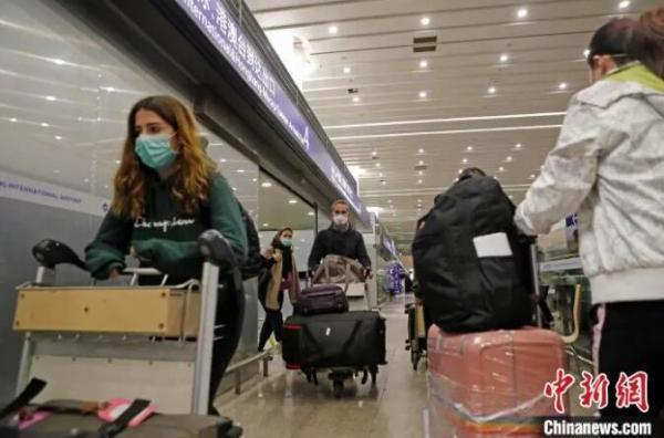 外籍入境人员推着行李前往上海16个区驻机场分流点。 殷立勤 摄