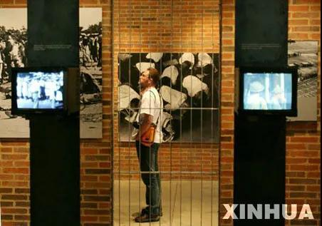 资料图:一名参观者在南非约翰内斯堡的种族隔离博物馆里观看展品。新华社记者 王迎 摄