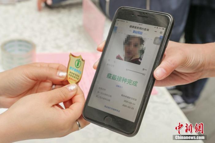"""3月29日,北京朝阳门街道在银河SOHO开展新冠疫苗接种集中宣传活动,为辖区楼宇内企业员工发放新冠疫苗接种倡议书和手机贴。员工今后进入该楼宇时,只需展示手机后面的手机贴即可进入。尚未接种新冠疫苗的员工,进入楼宇时,仍需扫描""""北京健康宝""""。目前,朝阳门街道已经为辖区12个商务楼制作新冠疫苗接种手机贴一万张。图为一名员工在领取手机贴前出示接种疫苗的凭证。 <a target='_blank' href='http://www.chinanews.com/'>中新社</a>记者 贾天勇 摄"""