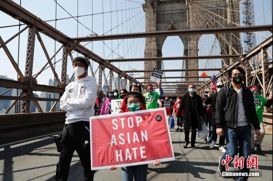 """当地时间4月4日,纽约举行反仇恨亚裔大游行。图为游行队伍中手持""""停止仇恨亚裔""""标语的亚裔孩童。记者 廖攀 摄"""