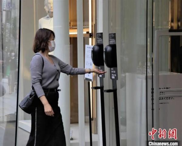资料图:图为东京市民进入商场前进行手指消毒。中新社记者 吕少威 摄