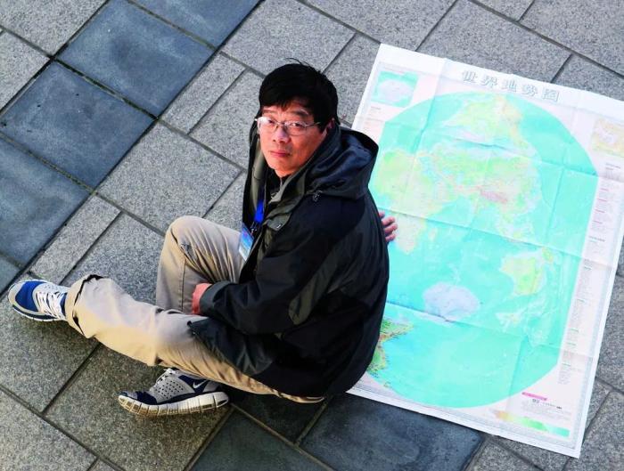 中国科学院精密测量科学与技术创新研究院郝晓光研究员与他创新编制的竖版世界地图。