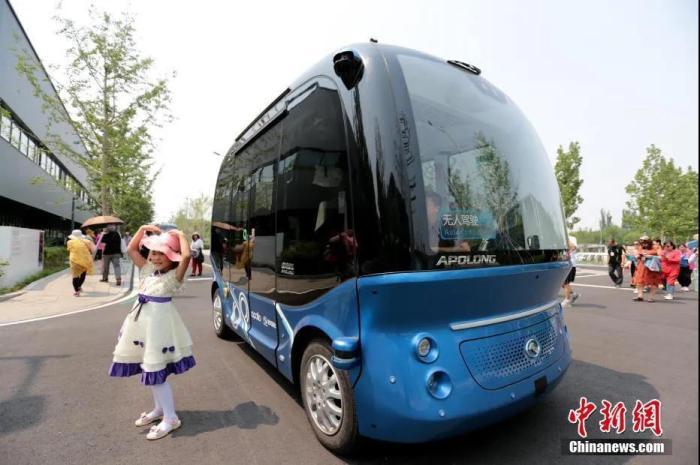 资料图:无人驾驶微循环电动巴士在雄安市民服务中心准备搭载乘客出行。 中新社记者 张远 摄