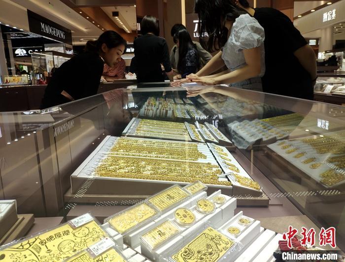 图为民众当日在福州一黄金饰品店挑选黄金饰品。<a target=