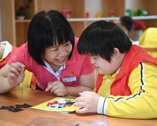 广东茂名市社会福利中心主任李兰(左)在跟院内儿童交流(4月27日摄)。新华社记者邓华摄