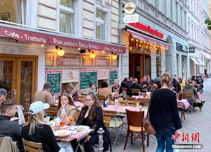 """5月21日,随着新冠疫情趋于缓和及疫苗接种铺开,德国首都柏林等多地开始重新允许餐馆和酒吧等在户外经营。与去年夏季""""解封""""相比,此次新增了一系列规定:用餐人士需出示新冠检测阴性报告、同桌不得超过五人(最多允许来自两个家庭)、每天23时至次日凌晨5时不得销售酒精饮料等。图为21日当晚,柏林的餐厅再度迎来用餐的顾客。 中新社记者 彭大伟 摄"""