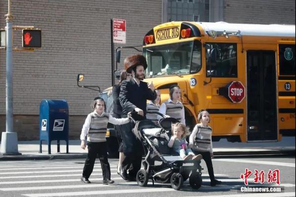 资料图:当地时间5月17日,民众从美国纽约∑ 市犹太社区的一所学校外经过。(廖攀 摄)