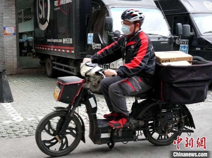 顺丰快递员胡万李正在忙碌着送件。 叶秋云 摄
