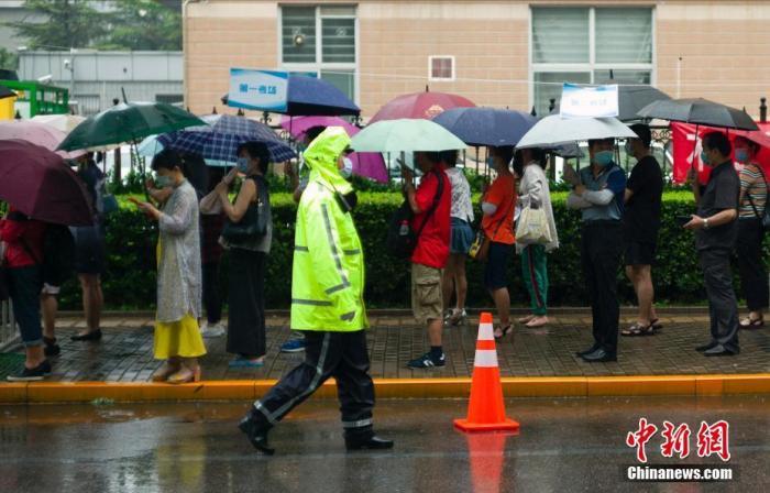 资料图:去年7月9日,北京中关村中学考点外,家长在雨中等待考生出考场。 中新社记者 盛佳鹏 摄