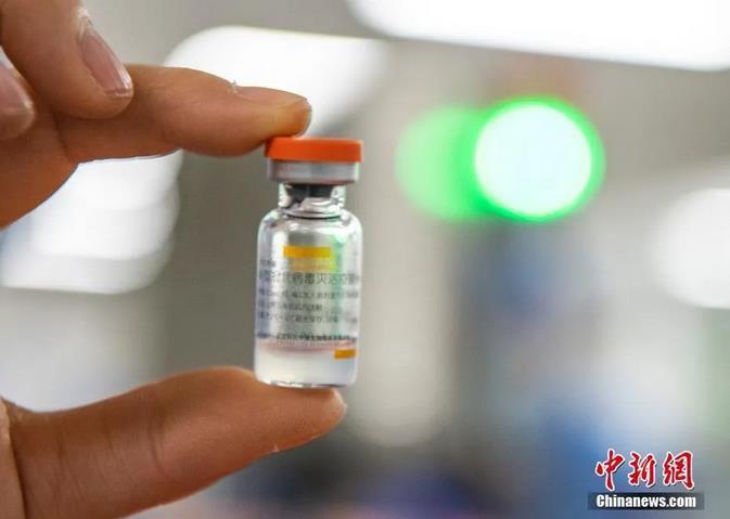 图为2021年1月6日,位于北京市大兴区的北京科兴中维生物技术有限公司的仓库内,工作人员展示一支西林瓶装新冠灭活疫苗。(资料图片)中新社记者 侯宇 摄