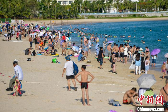 资料图:众多游客在三亚大东海旅游景区海滩享受碧海蓝天。 骆云飞 摄