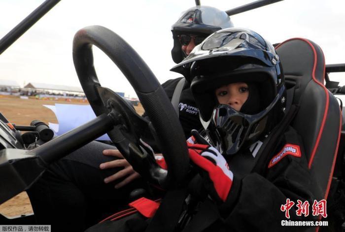 当地时间2021年2月20日,埃及吉萨,5岁的埃及萌娃Mansour Tarek开车参加汽车拉力赛,坐在身旁的是他的父亲、国际汽车拉力赛车手Tarek el-Erian。Mansour Tarek从小受到父亲的熏陶,渴望成为一名拉力赛车手。