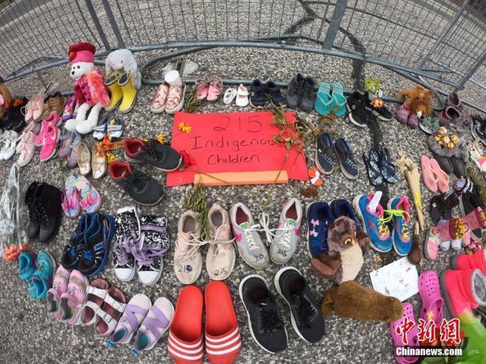 当地时间6月2日,在位于多伦多的加拿大安大略省省议会大楼门前,人们摆放了上百双童鞋和各式玩偶、鲜花、留言卡等,为该国一处原住民寄宿学校旧址发现215具儿童遗骸之事志哀。 <a target='_blank' href='http://www.chinanews.com/'>中新社</a>记者 余瑞冬 摄