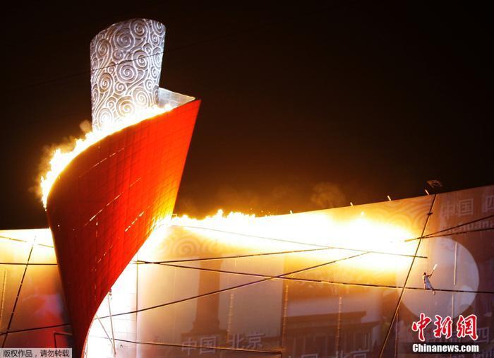 """资料图:2008年8月8日晚上8时整,北京奥运会开幕式在""""鸟巢""""正式举行。""""体操王子""""李宁以钢线吊到高空,""""空中漫步""""绕场一周后,点燃""""祥云""""造型的主火炬。"""