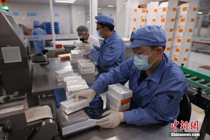 资料图:工作人员在对疫苗进行包装称重。 中新社记者 蒋启明 摄