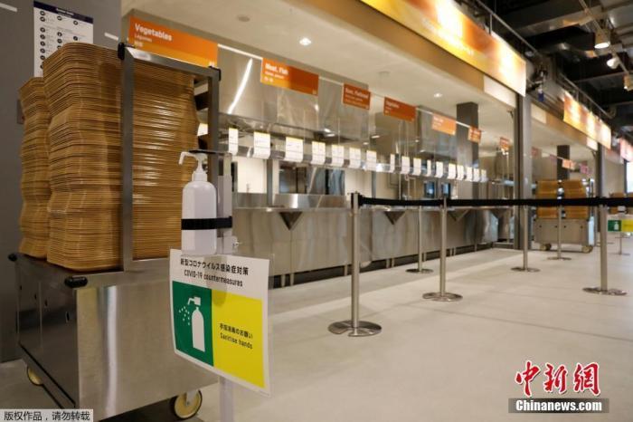 资料图:奥运村餐厅里摆放的洗手液和防疫标识。