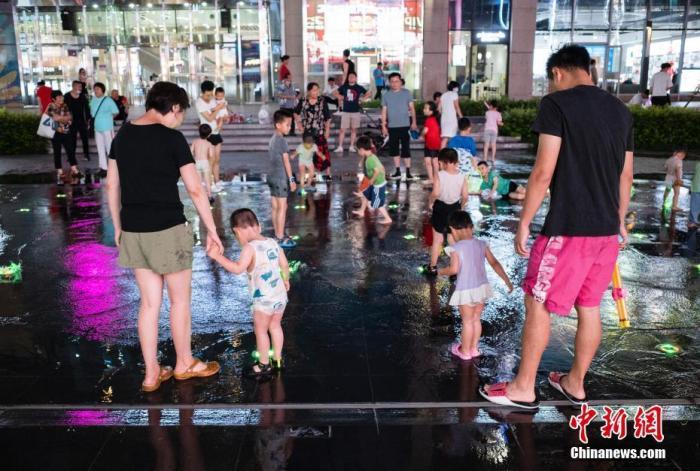 图为7月20日晚间,少年儿童在家长的陪伴下在北京市朝阳区望京小街的喷泉处玩耍。 中新社记者 侯宇 摄